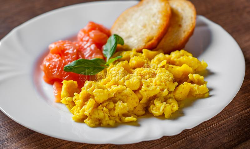 Scrambled eggs with smoked salmon and toast in white plate on wooden table royalty free stock photo