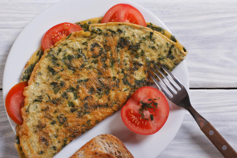 Scrambled eggs with spinach on the table stock photography