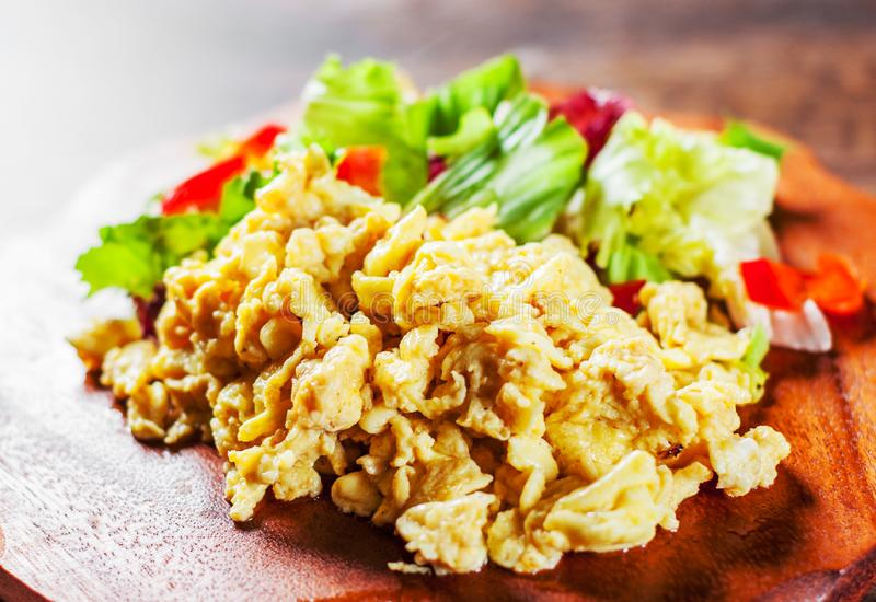 Scrambled eggs with various fresh mix salad leaves on wooden table royalty free stock image