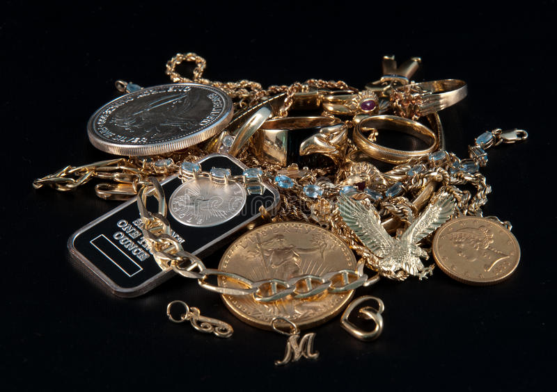 Scrap Gold & Silver Coins and Jewels. Close up of scrap gold, silver and jewels for cash on black background stock image