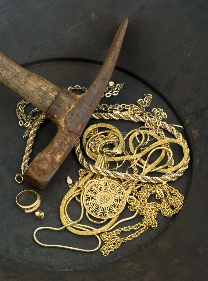 Scrap jewelry in gold pan with pick axe royalty free stock photos