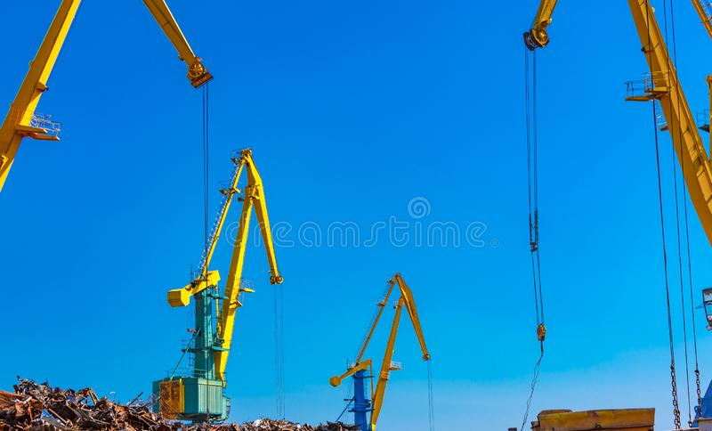 The scrap metal crane with a lot of metal in seaport stock images