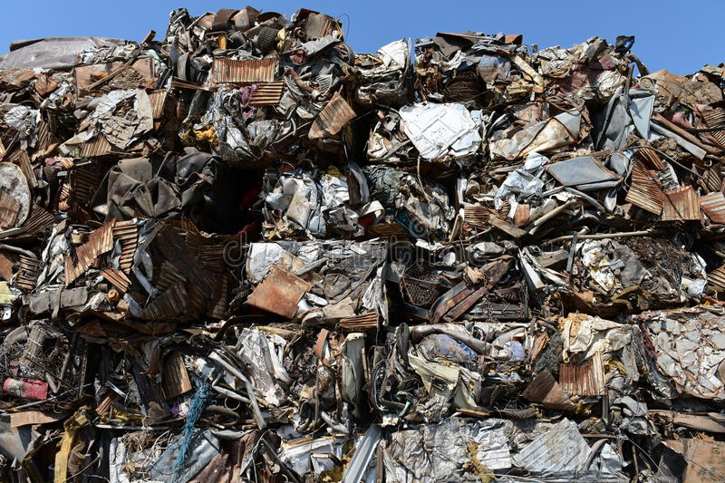 Stacked compressed crushed scrap metal for recycling. Large pile of stacked crushed cubed scrap metal at recycling scrapyard with blue sky royalty free stock photos
