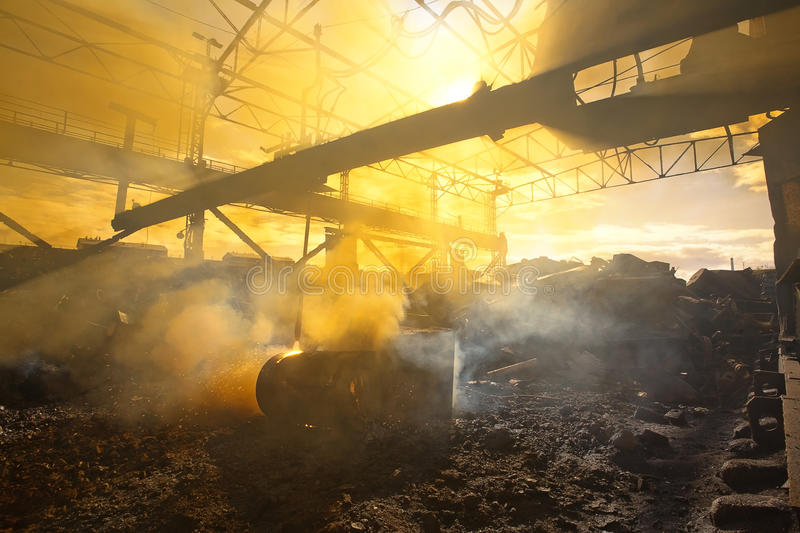 Scrap metal and smoke. Photo of scrap metal in the backyard of the factory and yellow smoke stock images