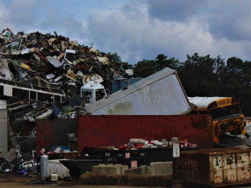 Scrap Pile. Giant scrap pile, alongside an old school bus, for recycling at a junk yard royalty free stock image