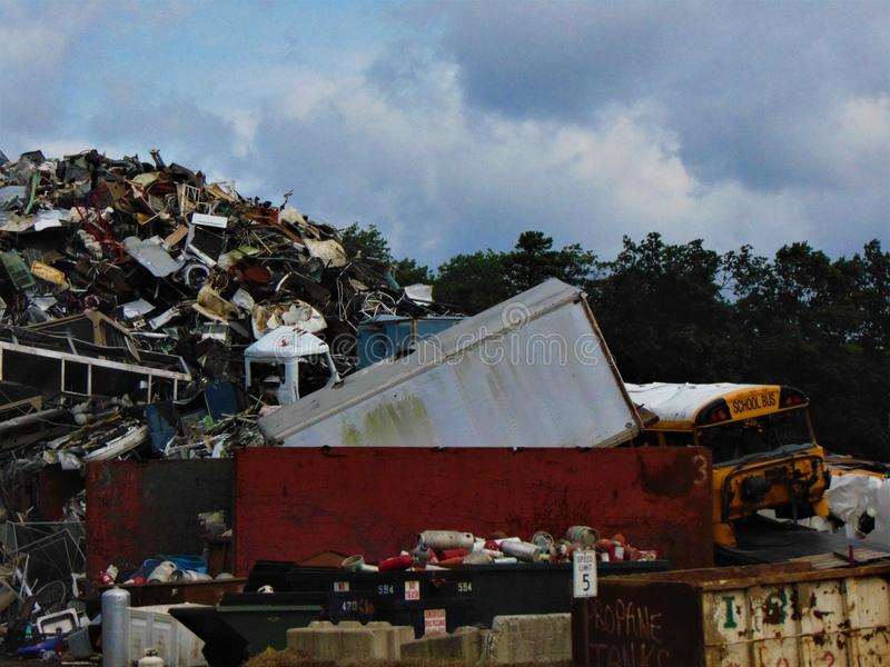 Scrap Pile. Giant scrap pile, alongside an old school bus, for recycling at a junk yard stock photo
