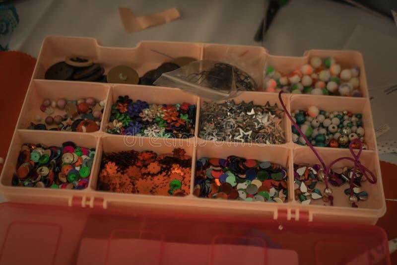 scrapbooking的各种各样的小项目在一个桃红色塑料盒 库存图片