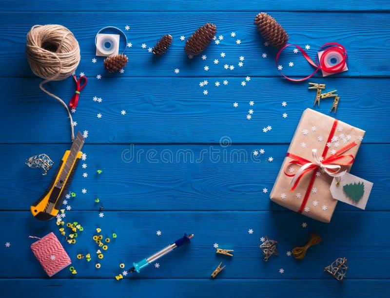 Scrapbooking De verpakking van een Kerstmisgift in kraftpapier-document op een blauwe houten achtergrond stock fotografie