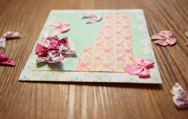 Scrapbooking elements and homemade greeting card on wooden background. Selective focus royalty free stock photos