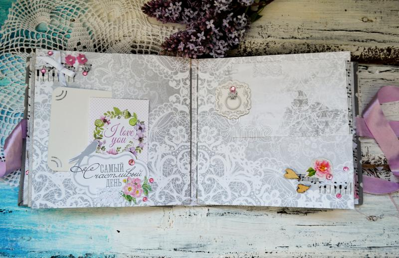 Scrapbooking handmade photo album. Diy. Top view on table with elements for scrapbooking, cut paper, die cuts, paper. Flowers, ribbons,embossing. Women hobby stock photography