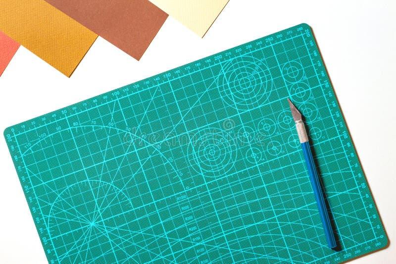 Scrapbooking Hintergrund der Papiergrafik Grüne Schneidematte und Messer mit farbigem Papier auf weißer Tabelle lizenzfreie stockfotos