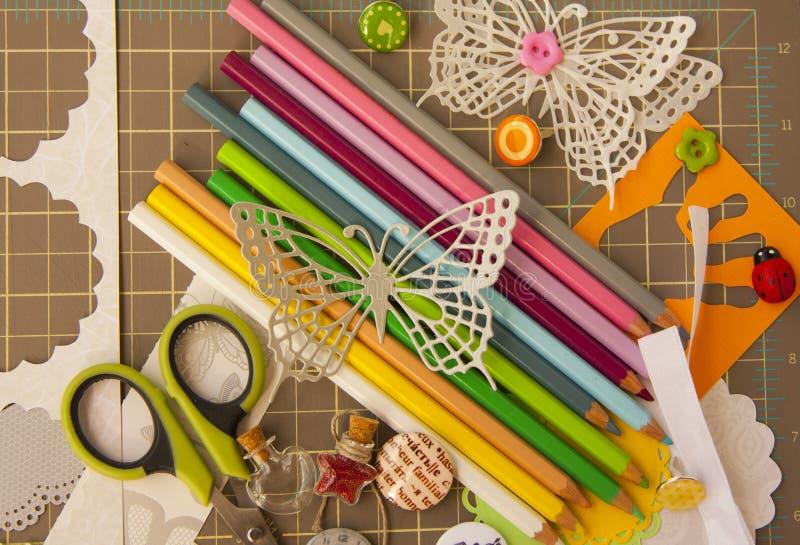 Scrapbooking och konstbakgrund med hjälpmedel, beståndsdelar, färgade blyertspennan och fjärilen arkivbild