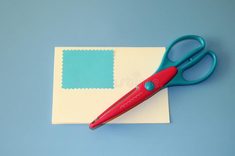 Scrapbooking scissors, wave pattern, colored paper blue cut out rectangle for greeting card royalty free stock photo