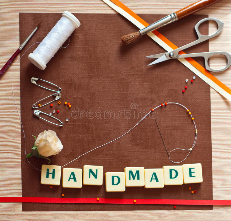Scrapbooking. Scrap booking set of materials � textured paper, brushes, spool of thread, needle, colorful beads, ribbons, artificial rose flower, letters on stock photos