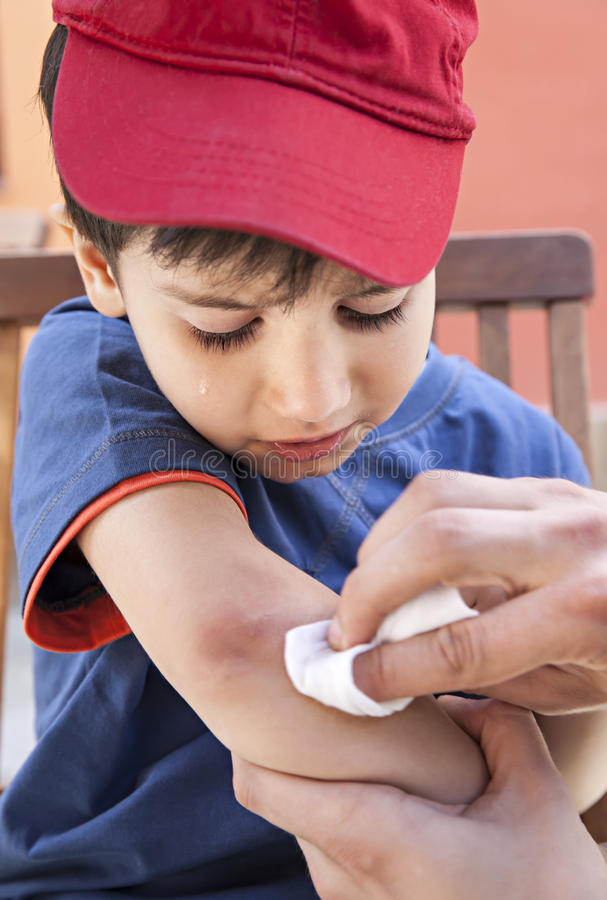 Scraped hand. Small boy crying in pain injuring his hand. Father provides first aid royalty free stock photos
