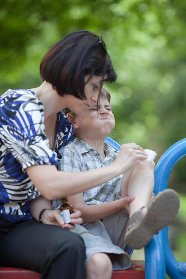 Scraped knee. Mum helping her son who scraped his knee royalty free stock photos