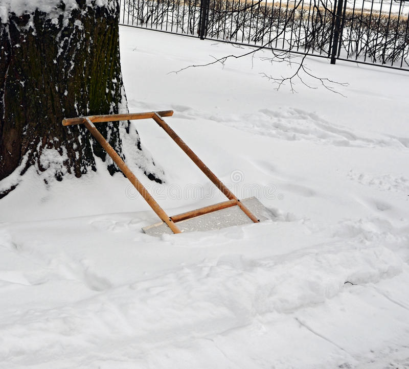 Scraper for remove snow in snowdrift near cleared-away path 2. Scraper for remove snow is leaned against a trunk of a big tree in a snowdrift near the cleared stock images