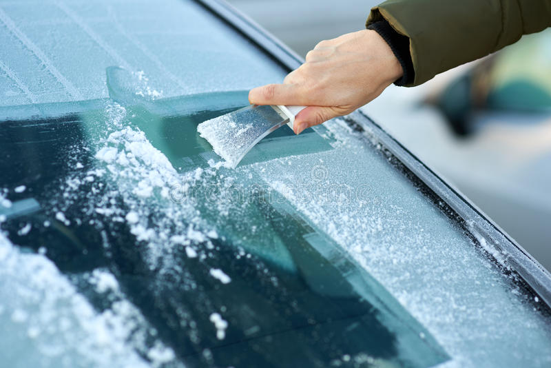 Scraping Ice Off the Windshield. Winter driving - scraping ice from a windshield stock images