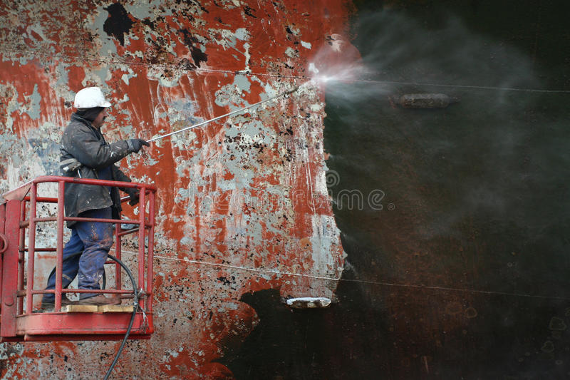 Scraping surface before painting ship stock image