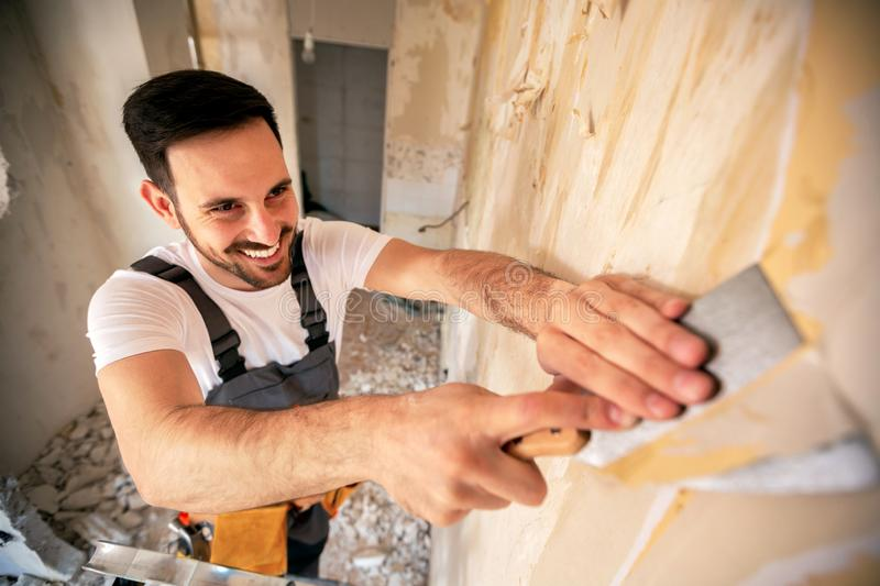 Scraping of wallpaper with a putty knife royalty free stock photo