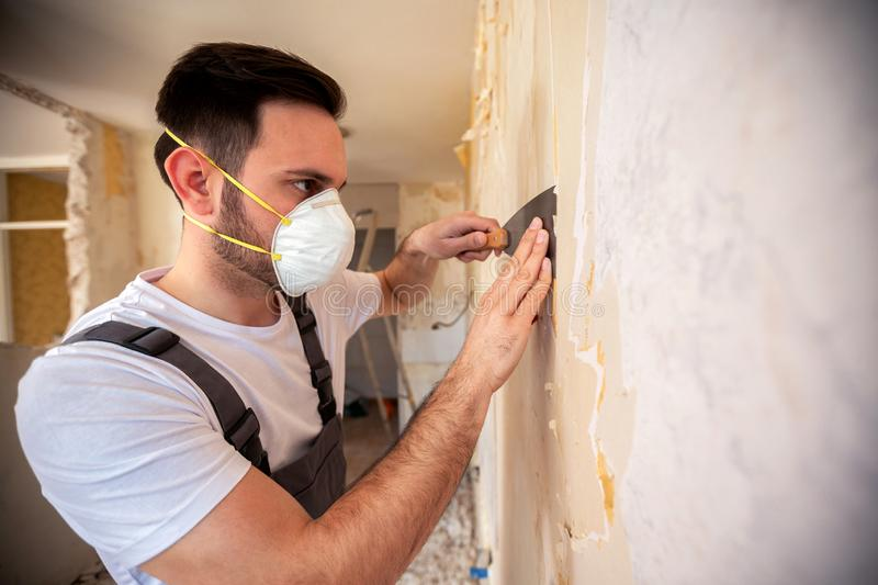 Scraping of wallpaper with a putty knife stock photo