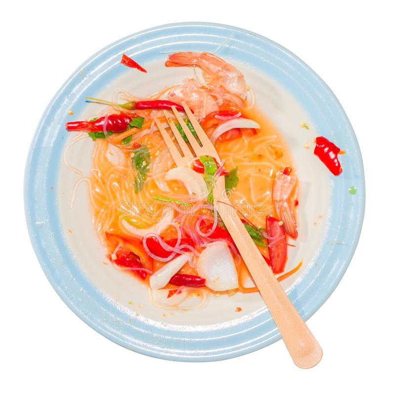 Scraps of food, red chili peppers, onion, orange carrots, coriander, vermicelli, shell shrimp and spoon in a dirty dish. Isolated. White background, Top view stock photography