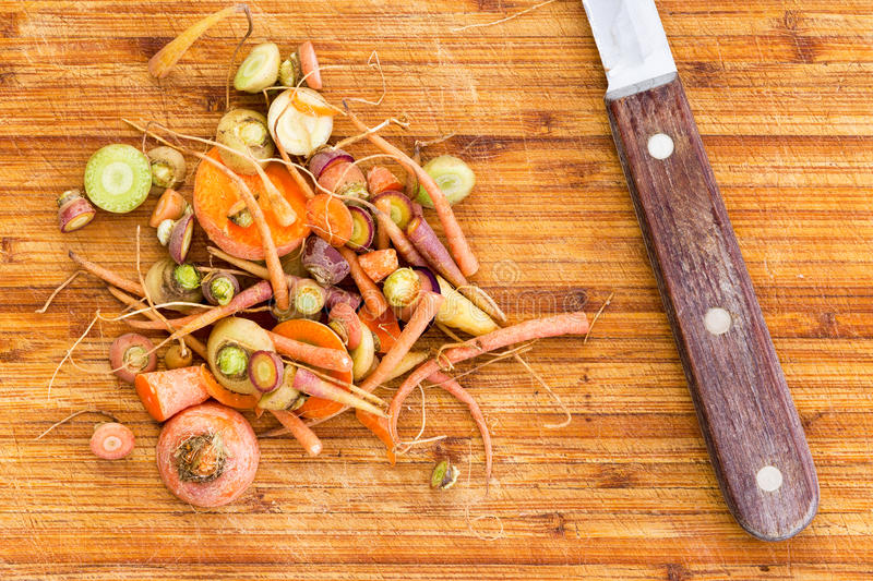 Scraps leftover from cutting carrots beside knife. Scraps leftover from cutting raw carrots beside knife over large wooden cutting board stock images