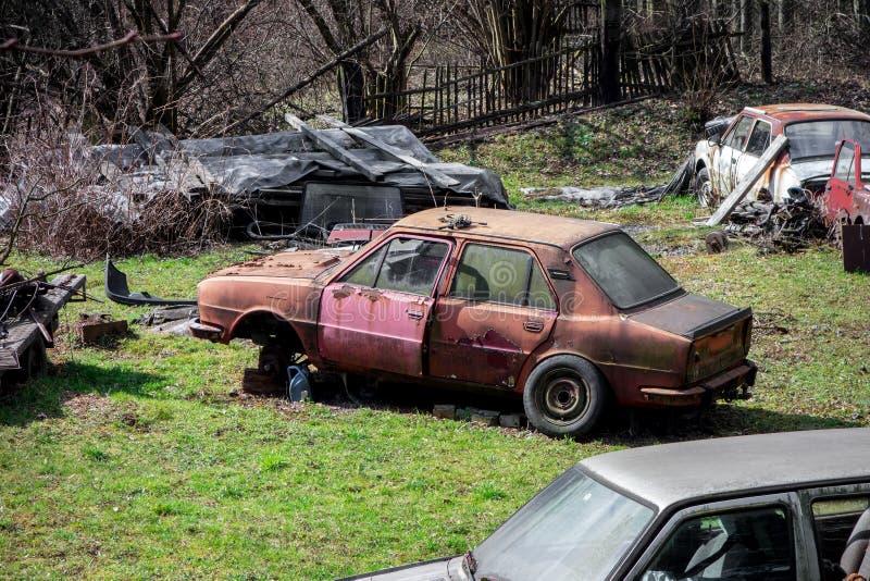 Scrapyard em um antigo jardim completamente de carros abandonados velhos imagens de stock