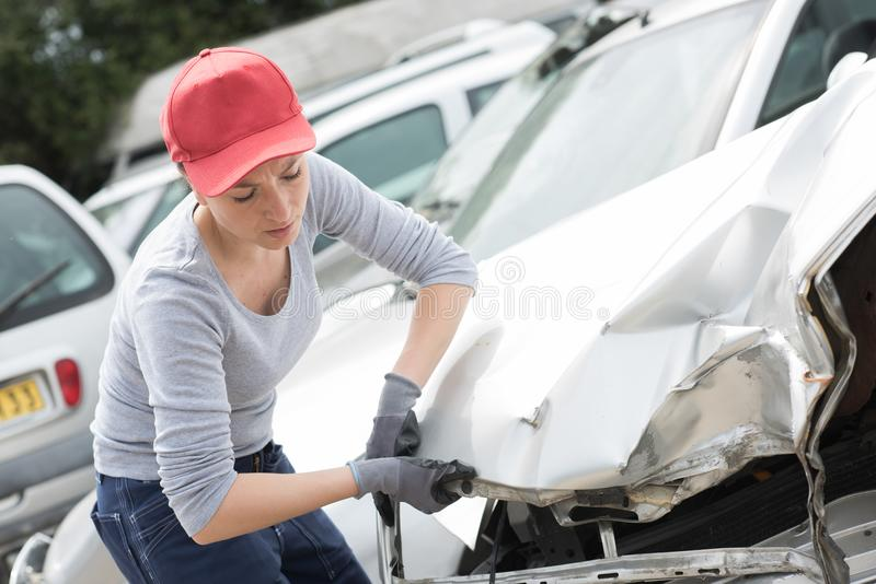 Scrapyard worker with accident damaged car. Accident stock photography