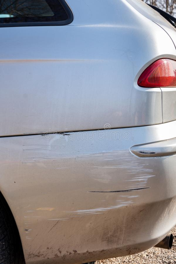 Scratched back bumper on the grey metallic car. Closeup image of damaged back bumper on the car. Photo for the insurance. Company of a scratched car stock photos
