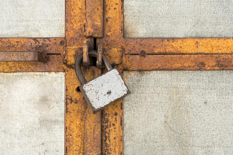 The scratched old padlock closes gray metal door or gate, abstract background royalty free stock image
