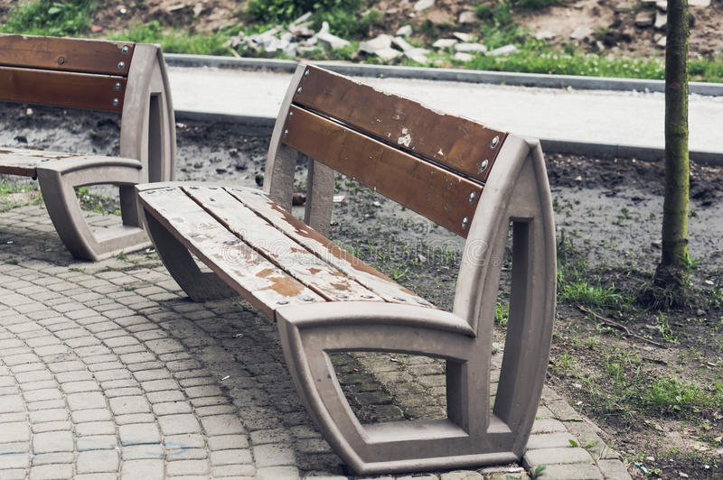 Scratched park bench. Old park bench with scratched brown paint in standard film look royalty free stock image