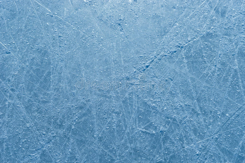 Scratched surface of ice rink strewn with the shards. Icy background for universal purposes stock photo