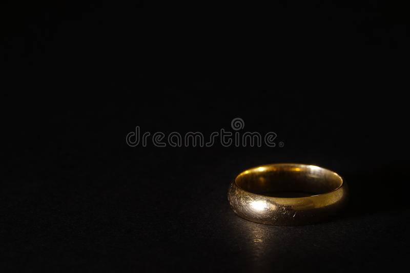 A scratched used old gold wedding ring on black background stock photos