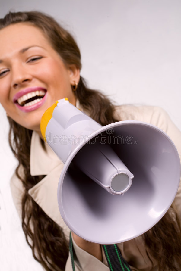 Screaming. Beautiful young girl with megaphone over white royalty free stock photo