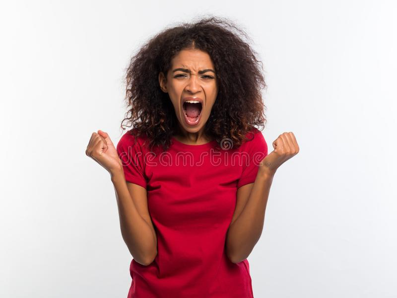Screaming african american woman in red top with closed eyes. Depressed angry black girl over white background in studio royalty free stock image
