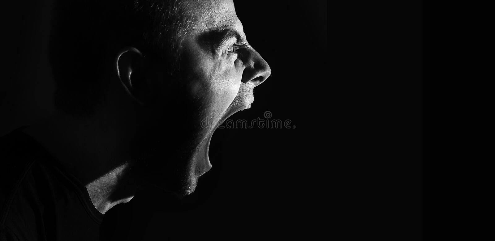 Screaming angry aggressive militant guy, man, black and white portrait, evil stock photography