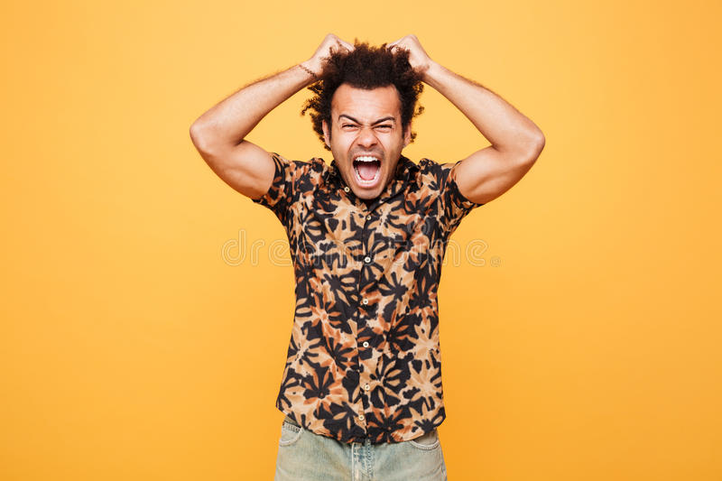 Screaming angry young african man standing over yellow background. royalty free stock image