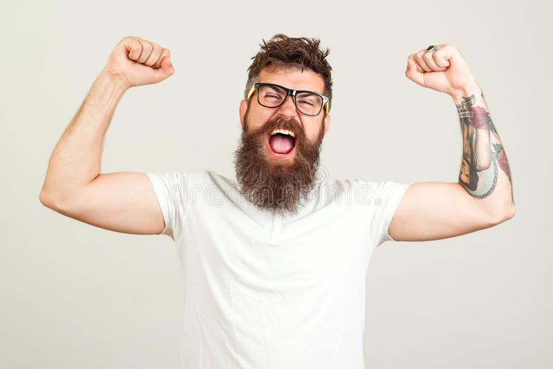 Screaming bearded brutal man with hands up. Excited bearded man in glasses celebrating success. Goal, Winner, Celebrating. Face royalty free stock photography