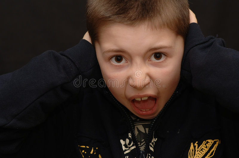 Screaming Boy. 9 year old boy with his mouth open in a scream, and his ears covered. Isolated on dark background stock photography