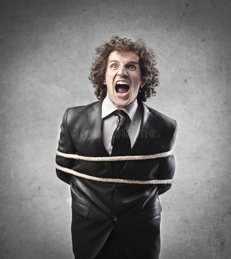 Screaming Businessman. A businessman tied with a rope is screaming royalty free stock photography