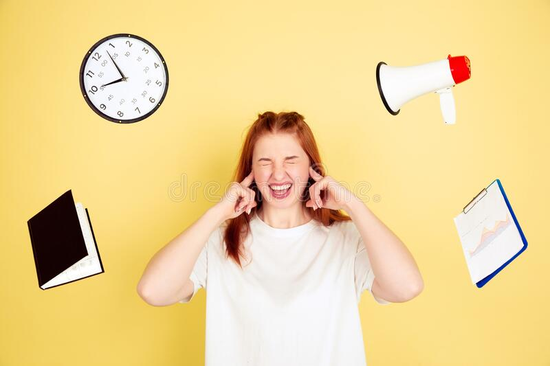 Caucasian young woman`s portrait on yellow background, too much tasks royalty free stock photography