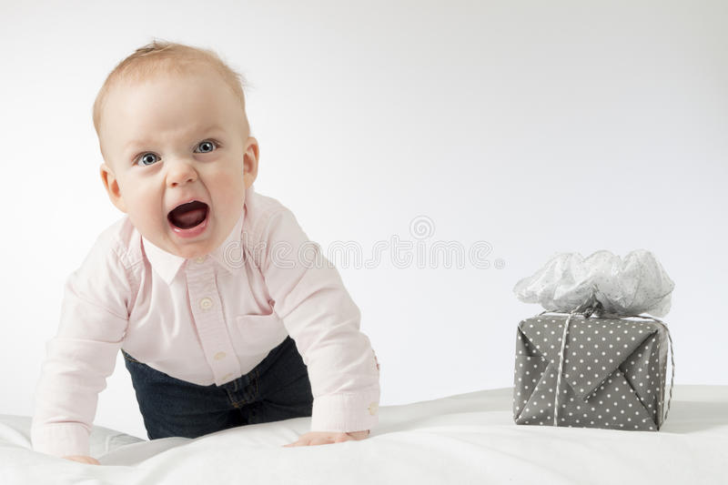 Screaming crawling infant baby looking at camera. Toddler kid with a gift on the white blanket. Horizontal stusio shot stock image