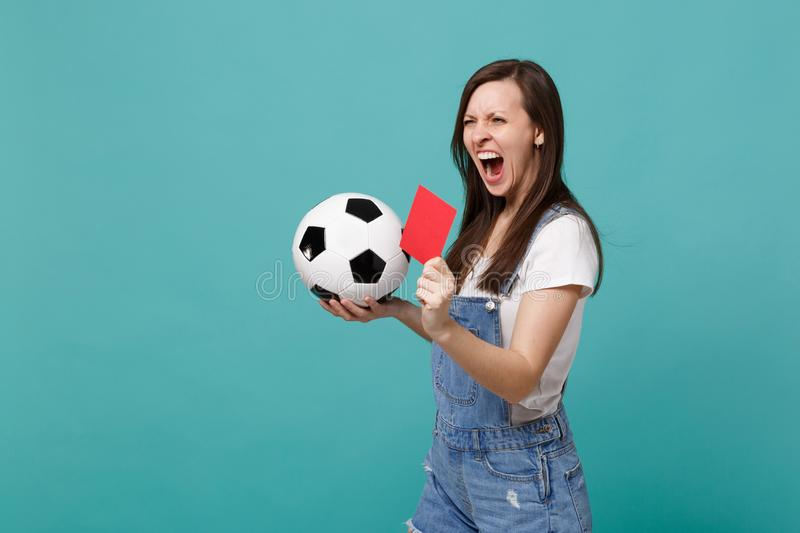 Screaming crazy young woman football fan support team with soccer ball, red card, propose player retire from field. Isolated on blue turquoise background stock image