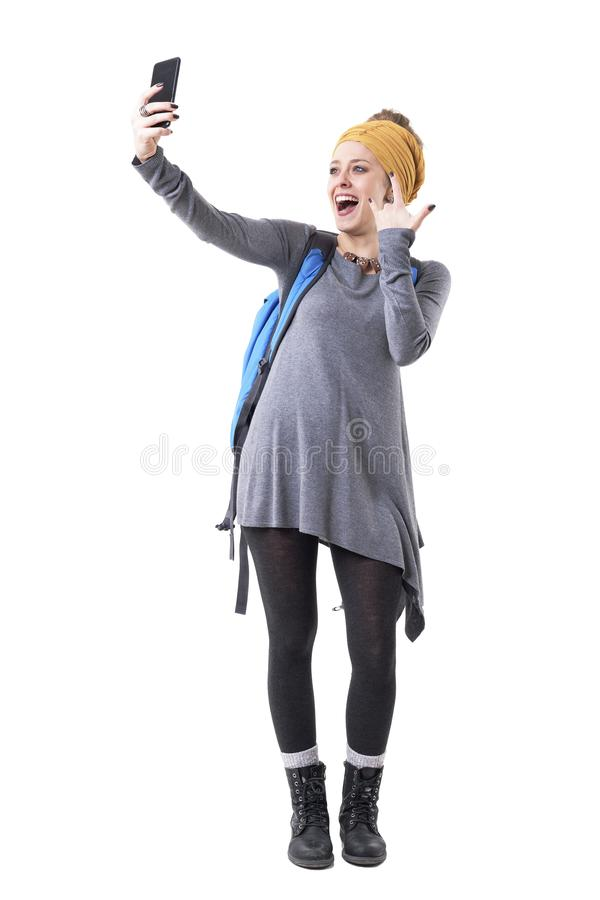 Screaming excited playful young stylish woman with backpack taking selfie with rock n roll sign. stock image