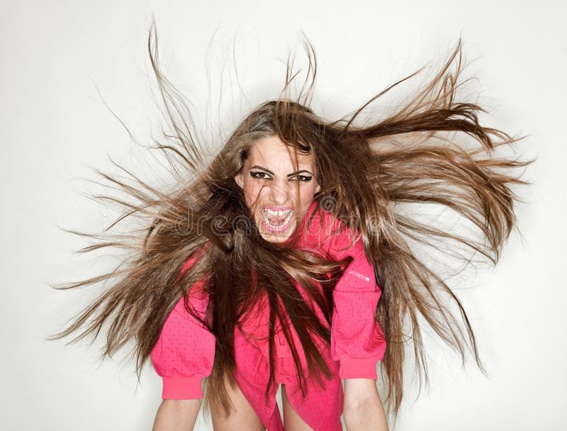 Screaming furious aggressive brunette lady. With flying long hairs, ring flash studio portrait on white stock photo