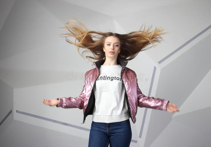 Screaming furious aggressive brunette woman with flying long hairs, flash studio portrait on modern wall royalty free stock photos