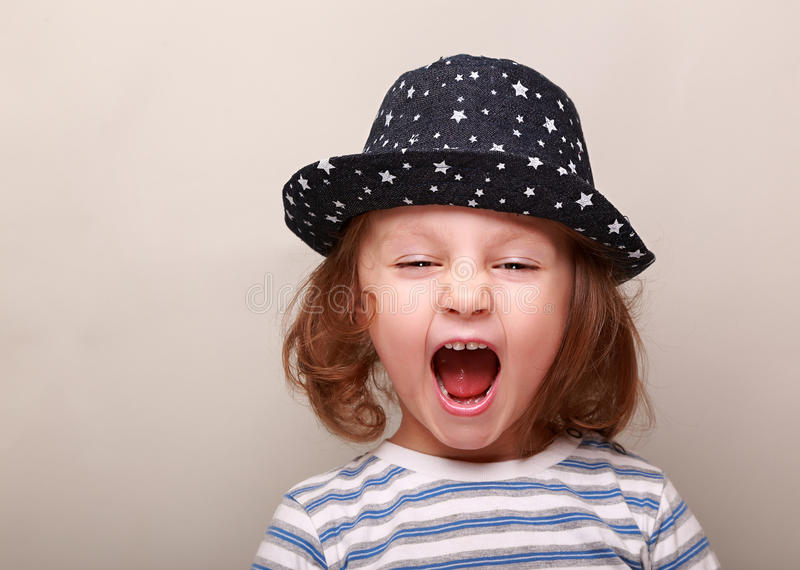 Screaming kid girl in hat with open mouth royalty free stock photo