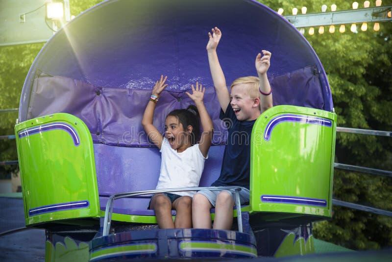 Screaming Kids enjoying a fun summer amusement park ride. Two screaming Kids enjoying a fun summer amusement park ride. Arms raised and laughing as they twirl stock photography