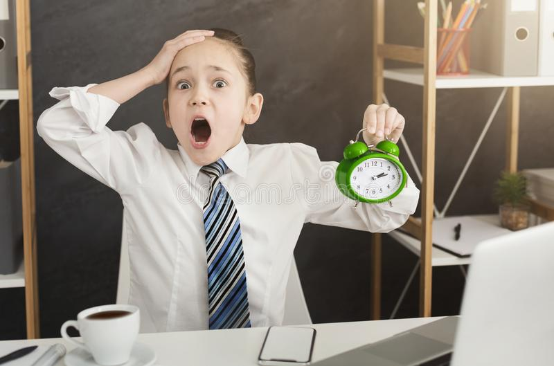 Screaming little girl with clock in office royalty free stock photos